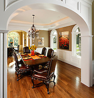 Traditional dining room framed by panelled archway.