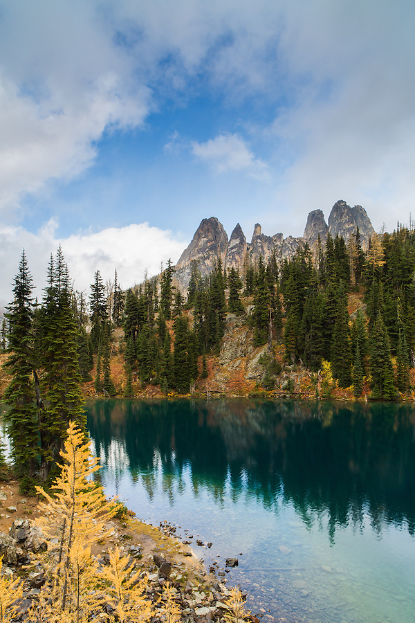 Blue Lake is seen with Early Winter Spires in the background on a partly cloudy day in Washington's North Cascades.