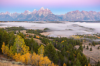 Grand Teton National Park, WY: Dawn light on the Teton Range with fog in the Snake River Valley in fall