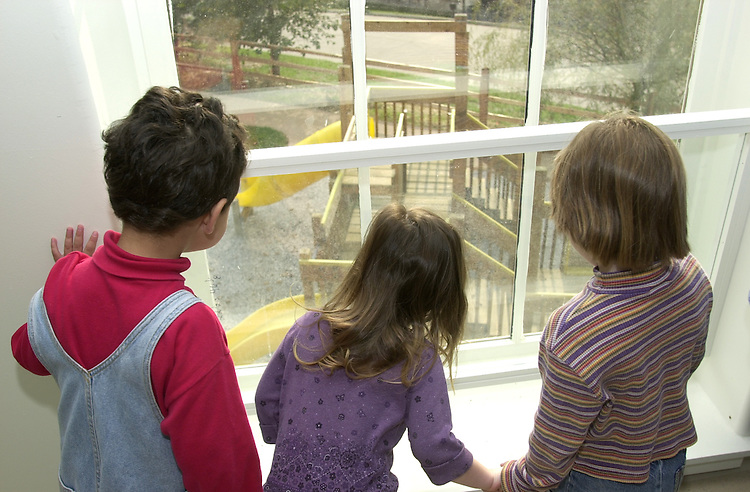 Daniel Wasserman (left), Ruby Cribbet (middle), Nicole Baringer (right) look at the playground from inside the new childcare Development Center.