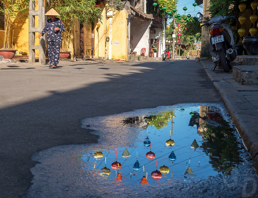 Old Town Hội An, the city's historic district, is recognized as an exceptionally well-preserved example of a South-East Asian trading port dating from the 15th to the 19th century and is a world UNESCO heritage Site. Reflecting Lanterns in water puddle, Hoi An Reflection in the street after a rain shower.