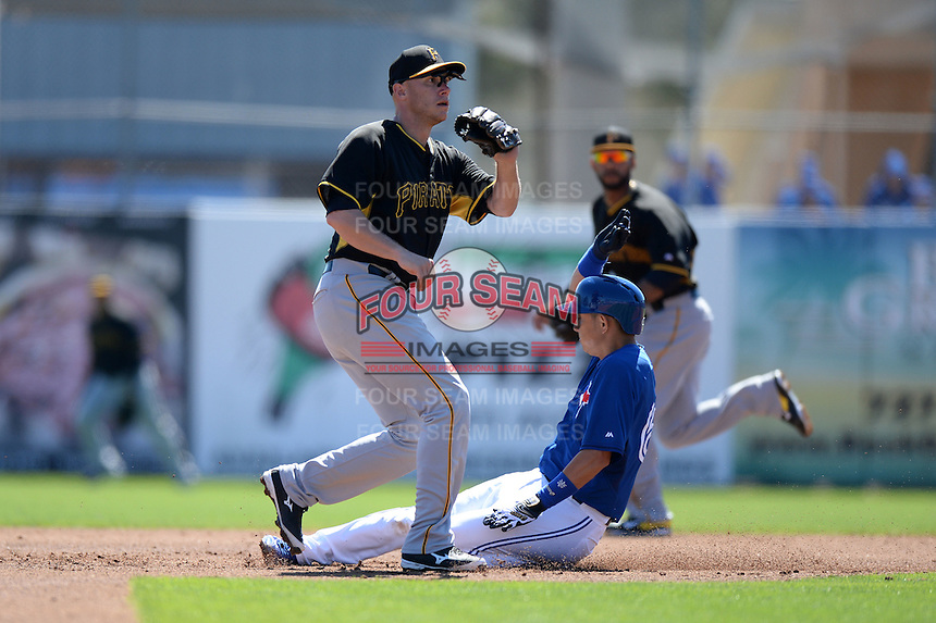 Infielder Clint Barmes (12) of the Pittsburgh Pirates waits for a throw as Munenori Kawasaki (66) slides in during a spring training game against the Toronto Blue Jays on February 28, 2014 at Florida Auto Exchange Stadium in Dunedin, Florida.  Toronto defeated Pittsburgh 4-2.  (Mike Janes/Four Seam Images)