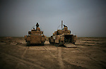 A pair of Bradley fighting vehicles and their crews wait for a mission in the desert on the outskirts of Baqubah, Iraq on Sunday May 27, 2007.