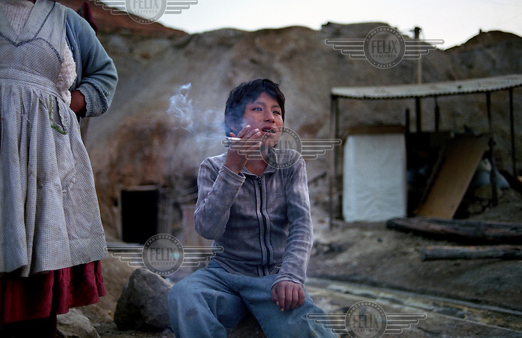11 year old Santiago Solis smokes a cigarette in front of his house on Cerro Rico (rich mountain). His father died in a mine accident and he lives with his mother. They scour for pieces of silver left in the discarded rocks from the mine. Silver ore deposits on this mountain provide jobs for over 20,000 miners in the town of Potosi. The number of mines in the area is estimated at 500... .