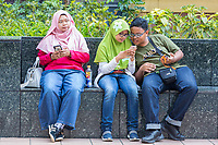 Singapore, Orchard Road Street Scene.  Young Singaporeans with their Cell Phones.