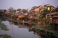 Houses on stilts in bad condition next to a river, Vietnam.