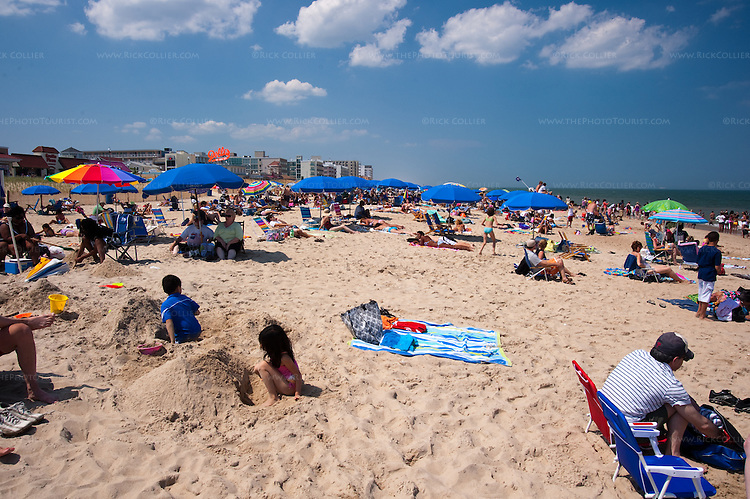 Children work on sand constructions amid sunbathers and beachgoers on the first day of summer at Rehoboth Beach, Delaware, USA.