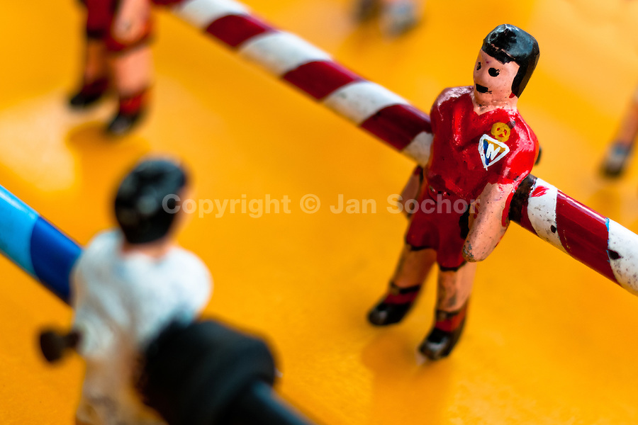 A table football player figure, with a painted red shirt, is seen inside the table football box on the street of Pesillo, a small village in the mountains of Ecuador, 26 June 2010. Table football, also known as futbolin in Latin America, is a widely popular table-top game in Ecuador. During the annual fairs, the rusty old outdoor-designed tables, fully ocuppied by excited children, may be found on all public places, particularly on the squares and in the parks. Human players use figures mounted on rotating bars to kick the small plastic ball into the opposing goal. Each team of 1 or 2 human players controls 4 rows on its side of the table. The game ends when one team scores a predetermined number of goals. In 2002, the International Table Soccer Federation (ITSF) was established to promote the sport of table football.