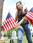 WINSTED CT. 18 May 2018-051818SV02- Georgi Andrews of Winsted replaces old American Flags with new one at a cemetery on Oak Street in Winsted Friday. Andrews and her children help replace the flags at that cemetery every year before Memorial Day.<br /> Steven Valenti Republican-American