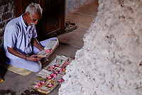 INDIA Madhya Pradesh , organic cotton project bioRe in Kasrawad , cotton farmer having a prayer beside his cotton yield at home / INDIEN Madhya Pradesh , bioRe Projekt fuer biodynamischen Anbau von Baumwolle in Kasrawad, Baumwollfarmer bei einem Gebet neben seiner Baumwollernte zu Hause