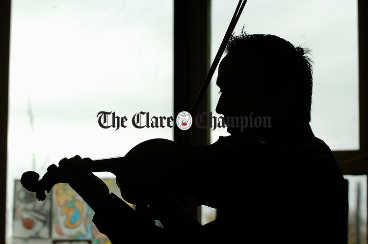 Tutor Oisin Mac Diarmada is silhouetted against the window in his class during the Ennis Trad Festival. Photograph by John Kelly.