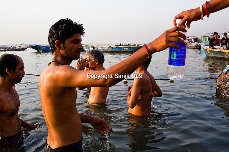 A young man takes a bottle to fill ganges water for a woman on the ghats in the ancient city of Varanasi in Uttar Pradesh, India. Photograph: Sanjit Das/Panos