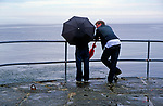 AE2MGD Young couple with umbrella in rainy weather looking out to sea from the end of a pier