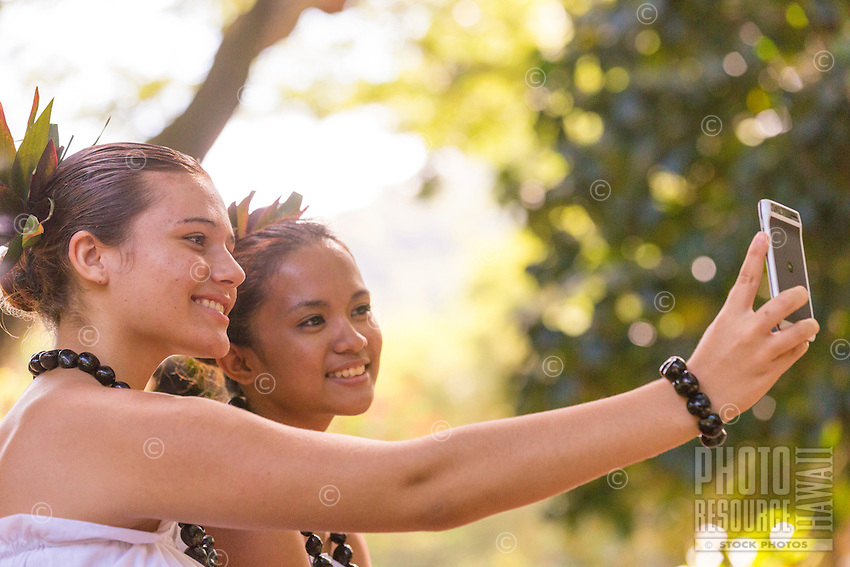 "Young hula dancers do a self-portrait (or ""selfie"") with a smartphone at a recital in Waimea Valley on O'ahu."