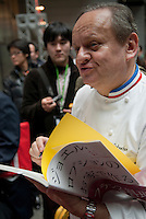 Chef Joel Robuchon signs a book at Tokyo Taste, The World Summit of Gastronomy 2009, 10 February 2009,Tokyo, Japan.Many of the world's top chefs are assembled for the sold-out 3 day event in the center of Tokyo.