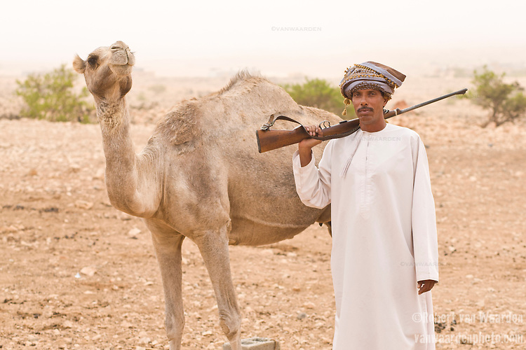 A bedouin man posing with a rifle and camel in Jabal Samhan, Oman