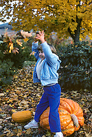 Child throwing leaves up in play on pumpkin. Oregon