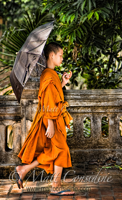 This young monk looks deep in concentration as he walks beside the Mekong.<br /> (Photo by Matt Considine - Images of Asia Collection)
