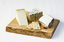 Three cheeses with crackers on a cutting board