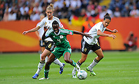 Celia Okoyino da Mbabi (r) and Simone Laudehr (l) of team Germany and Perpetua Nkwocha of team Nigeria during the FIFA Women's World Cup at the FIFA Stadium in Frankfurt, Germany on June 30th, 2011.