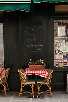 Outdoor tables at a Parisian cafe, with checked table cloths and a chalkboard menu, Paris, France.