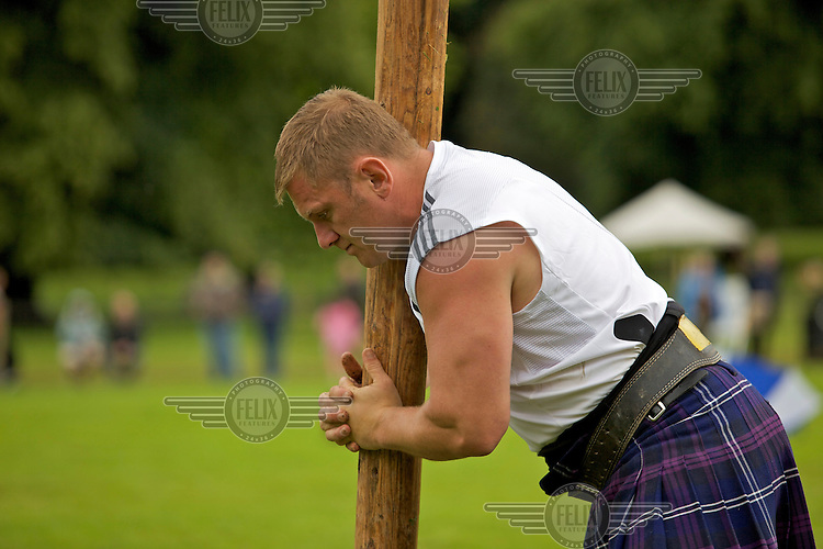 A man wearing a kilt competes in the World Championships for caber tossing, the hardest of the heavy events at the Inveraray Highland Games, held at Inveraray Castle in Argyll.