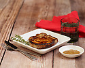 Grilled pork chop served on a white plate with thyme and mustard
