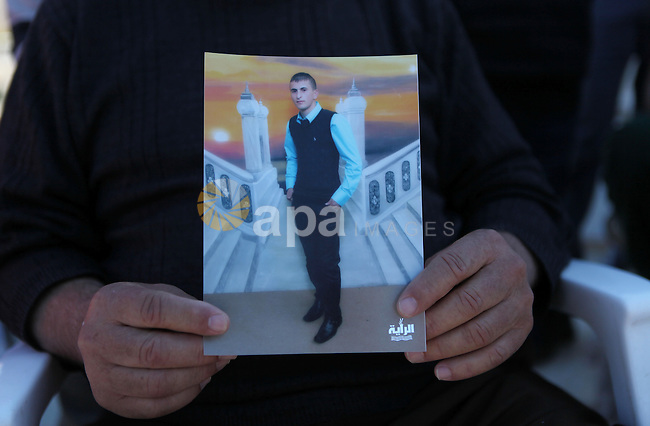 Grandfather of Hammam Hammam Masalma, the suspect in hit-and-run that left three soldiers injured, holds Hammam's picture, at his house in Beit Awwa, near the West Bank city of Hebron, November 6, 2014. The hit-and-run incident on the main Bethlehem-Hebron road on Wednesday night was the third such vehicular attack on Israeli soldiers and civilians in recent weeks, although the previous two took place in Jerusalem. Photo by Mamoun Wazwaz
