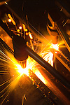 Welders cutting steel for barge assembly