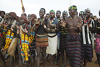 Ethiopia. Southern Nations, Nationalities, and Peoples' Region. Omo Valley. Turmi. Hamar tribe (also spelled Hamer). Pastoralist group. Hamar men and women sing, clap their hands and welcome the foreign visitors to their village. Hamar women wear an elaborately decorated goatskin, often colored with beads and cowries. Beaded necklaces, bracelets and waistbands adorn their bodies. Hamer women indulge in elaborate hairdressing by decorating their hair with clay and butter twisted into a striking long plait. As a custom, every Hamer man carries a wooden headrest which doubles as a stool. The Omo Valley, situated in Africa's Great Rift Valley, is home to an estimated 200,000 indigenous peoples who have lived there for millennia. Amongst them are 60'000 to 70'000 Hamar, an Omotic community inhabiting southwestern Ethiopia. They live in Hamer woreda (or district), a fertile part of the Omo River valley, in the Debub Omo Zone of the Southern Nations, Nationalities, and Peoples Region (often abbreviated as SNNPR) which is one of the nine ethnic divisions of Ethiopia. 7.11.15 © 2015 Didier Ruef