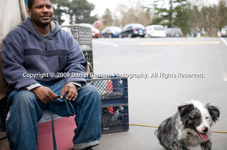 Vashawn Wanzer, 32, sits near the entrance to Tent City 3, with the camp's dog Lucky. Wanzer has lived in Tent City 3 for the past nine months. He says he did not sleep indoors this winter.