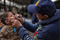 A Pakistani health worker administers polio drops to children before boarding to the train departing from Karachi city to other provinces at the railway station in Karachi, Pakistan on Jan. 08, 2014
