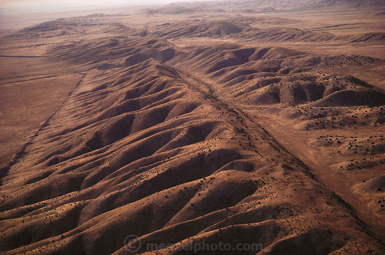 """Aerial photograph of the San Andreas Fault in California as it crosses the Carrizo Plain. The Earth's crust is fractured into a series of """"plates"""" that have been moving very slowly over the Earth's surface for millions of years. Two of these moving plates meet in western California; the boundary between them is the San Andreas fault. The Pacific Plate (on the west) moves northwestward relative to the North American Plate (on the east), causing earthquakes along the fault. The San Andreas is the """"master"""" fault of an intricate fault network that cuts through rocks of the California coastal region."""