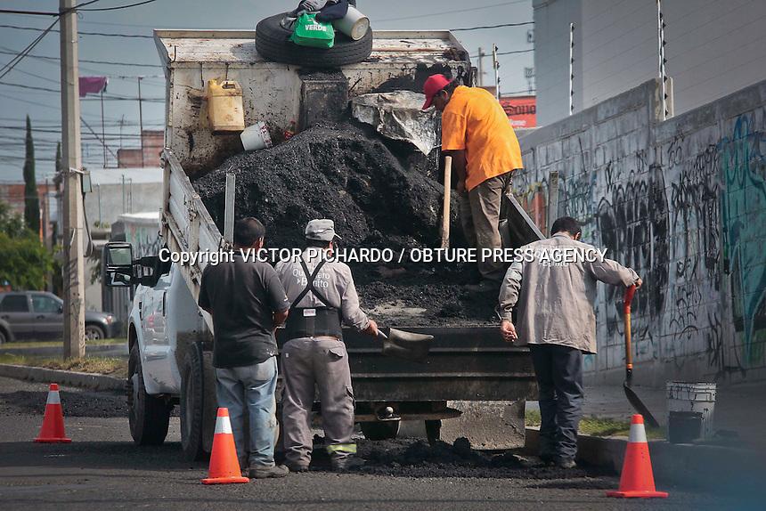 Querétaro, Qro. 24 junio 2015.- Cuadrillas de trabajadores del municipio de Querétaro trabajan en labores de bacheo luego de las constantes lluvias registradas en día anteriores. Foto: Victor Pichardo / Obture Press Agency
