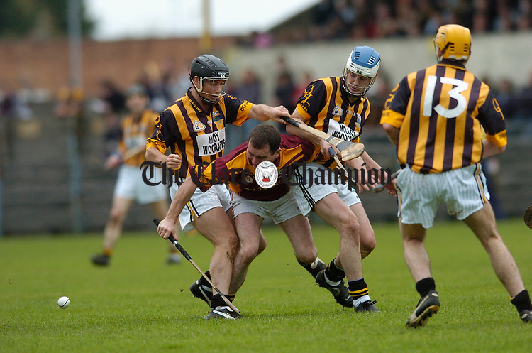 Tulla's Brian Quinn is sandwiched between Ogonnelloe's David Forde and Patrick Barton during the Senior B hurling final at Cusack park. Photograph by John Kelly.
