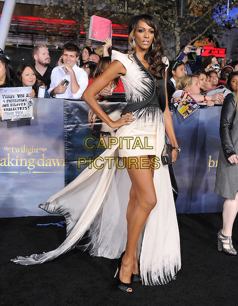 "Judi Shekoni.""The Twilight Saga: Breaking Dawn - Part 2"" Los Angeles Premiere held at Nokia Theatre L.A. Live, Los Angeles, California, USA..November 12th, 2012 .full length dress cream white black train mini clutch bag hand on hip.CAP/DVS.©DVS/Capital Pictures."