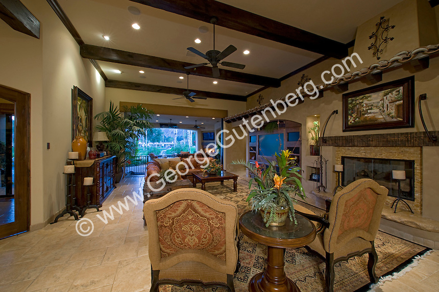 Mediterranean decore family room featuring beamed ceilings, elegant furnishings and pocketed doors that open to the outside