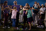 Dawn Sult, left, and Carrie Court, right hug their daughters at a vigil for the Granite Mountain Hotshots, 19 of who perished in the Yarnell Fire Sunday at Prescott High School in Prescott, Arizona, July 2, 2013.