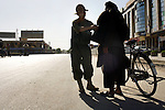 An Afghan National Army soldier searches a man on a bicycle near a main square in the city of Kandahar, Afghanistan, Thursday, Aug. 20, 2009. The streets of the city were bare, as residents were not allowed to drive cars or trucks on election day, a measure to prevent car bombs at polling stations and elsewhere.
