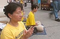(040831-SWR445.jpg) New York, NY - 31 August 2004 - Practioners of Falun Gong ( Falun Dafa ) mediitate on the corner of Houston Street and Broadway in the Soho section of New York.