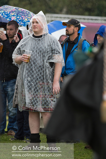 Two men dressed in kilts and rain ponchos during events at Bannockburn Live, at Bannockburn, Stirlingshire. The re-enactment marked the 700th anniversary of the Battle of Bannockburn, where the Scots army under Robert the Bruce defeated the English army of Edward II. The event was part of Scotland's Year of Homecoming celebrations and was attended by a sell-out 10,000 crowd.