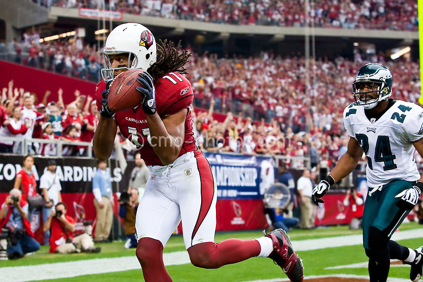 Jan 18, 2009; Glendale, AZ, USA; Arizona Cardinals wide receiver Larry Fitzgerald (11) catches the second of three touchdown passes from Kurt Warner (not pictured) in front of Philadelphia Eagles cornerback Sheldon Brown (24) in the second quarter of the NFC Championship Game at University of Phoenix Stadium.  The Cardinals won the game 32-25 to advance to Super Bowl XLIII.