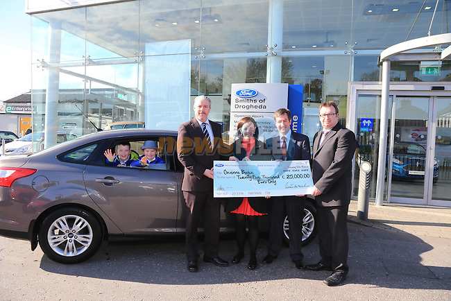 Grainne Boyce (2L) receiving her cheque for the price of her car back from Ciaran McMahon Ford Ireland (L) Nicky Smith and Niall Maroney N Smith and Sons pictured with  Ben and Jack Boyce in car..Picture: Fran Caffrey / www.newsfile.ie ..