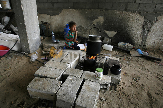 "A Palestinian boy sits near firewood in a destroyed house in Khan Yunis in the southern Gaza Strip on September 11, 2014. Israel's deputy foreign minister,Tzahi Hanegbi , warned that Hamas was likely to resume ""violence"" if it feels it has made no political gains from upcoming talks in Cairo. Photo by Abed Rahim Khatib"