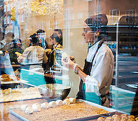 A pastry worker prepares merveilleux (wonderfuls) in the window of Aux Merveilleux du Fred in Greenwich Village in New York on Sunday, April 5, 2015. Merveilleux are confections made of two meringues stuck together with whipped cream, then coated with whipped cream and then coated with chocolate or other flavors. (© Richard B. Levine)