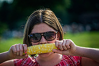 Freckled face young girl eats raw corn bought at a local farmers market.