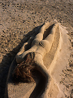 Surfer Girl Laying on Surfboard Sand Sculpture, Kailua Beach Park, Oahu, Hawaii, USA.