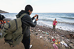 One refugee photographs another on a beach near Molyvos, on the Greek island of Lesbos, on October 31, 2015. They arrived on a boat full of refugees from Turkey. They were received by local and international volunteers, then proceeded on their way toward western Europe. The boat was provided by Turkish traffickers to whom the refugees paid huge sums to arrive in Greece.