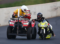 Jul. 18, 2014; Morrison, CO, USA; NHRA pro stock motorcycle rider Steve Johnson talking with a Safety Safari quad rider as he catches a ride during qualifying for the Mile High Nationals at Bandimere Speedway. Mandatory Credit: Mark J. Rebilas-
