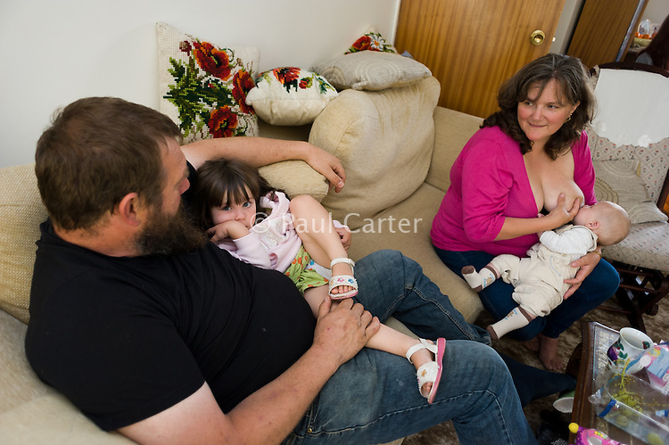 A mother breastfeeding her baby in the living room at a family gathering.<br /> <br /> 23 August 2011<br /> Hampshire, England, UK